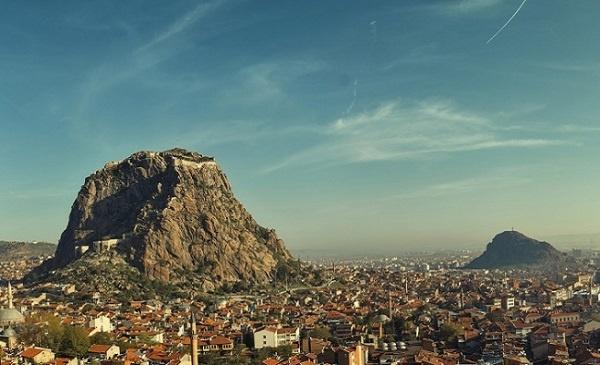 Afyon Kalesi   Tarihi Afyonkarahisar Kalesi tüm şehre hâkim bir kayalıktan oluşmaktadır. Doğal koruma imkânına sahip müstakim konumundan dolayı vaktiyle şehrin savunmasında hayati önemi haizdi. Geçtiğimiz yüzyılın ilk çeyreğine kadar bu önemini korumuştur. Günümüzde gezginlerin veya turistlerin uğrak yeridir. Sarp kayalık ve dik bir yapı görünümünde olan kale, surlarla çevrelenmiş ve kadim zamanlardan beri savunma amaçlı olarak şekillendirilmiştir. Kaleye çıkmak için 600 basamaktan oluşan merdivenleri tek tek çıkmanız gerekir.  Mevlevihane'den kalenin tepesine bakınca boynunuzun ağrıdığını hissediyorsunuz. Kaleye Afyonlu mihmandarımız Yusuf ve Ali kardeşlerimizle birlikte çıkıyoruz. Kaleden tarihi camilere bakınca tüm yapıların minarelerinde tuğla malzemelerin kullanıldığı görülür. Kale yolu üzerinde bir çay bahçesi var. Semaver çayının lezzeti Afyonkarahisar'ın soğukluğunu unuttuyor. Kale merdivenlerinden çıktıkça Eski Afyon şehrini daha net bir şekilde görüyoruz. Tarihi evler, şekil olarak kendine özgü bir model oluşturmuş. Tarihi çevreyi koruma, kültürel mirasa sahip çıkma adına Mevlevihane civarındaki bir beton evin yıkımına bizzat şahit olduk. Tepeden bakıldığında şehirdeki yegâne yeşil alanların cami civarları olduğu hemen fark ediliyor. Bütün büyük şehirlerimiz böyle değil mi? Yeşil alan olarak cami çevreleri ve mezarlık alanları kaldı. Onlarda maalesef günden güne erimekte!