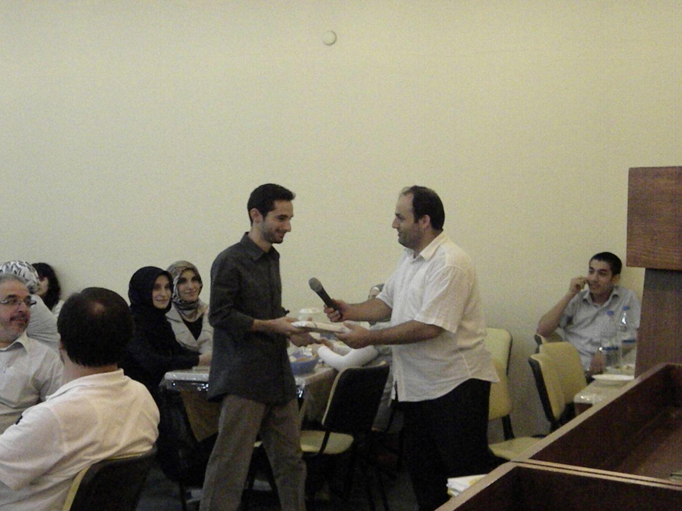 Asım Gültekin Yusuf Kot'a ödülünü verirken